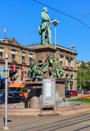 Zurich, Switzerland - 20 July, 2016: the monument to Alfred Escher on Bahnhofplatz square in Zurich, building of the Zurich main railway station in the background. Alfred Escher was a renowned Zurich politician, businessman and railway pioneer, the monume