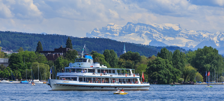 Zurich, Switzerland - 26 May, 2016: MS Limmat passing on Lake Zurich with passengers on board, summits of the Alps in the background. MS Limmat is a ship of the Lake Zurich Navigation Company, which is a Swiss public company, operating passenger ships and