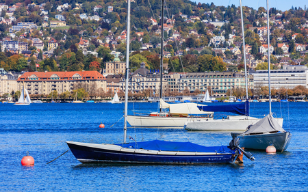 Sailboats on Lake Zurich in Switzerland, buildings of the city of Zurich in the background, selective focus on the boats. The picture was taken in the beginning of October. Stock Photo