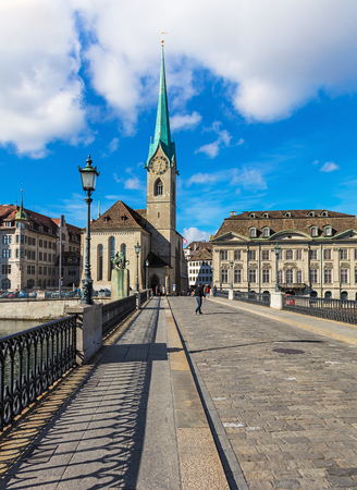 Zurich, Switzerland - 7 October, 2017: view along Munsterbrucke bridge towards the Fraumunster cathedral. Munsterbrucke is a pedestrian and road bridge over the Limmat river, listed in the Swiss inventory of cultural property of national and regional sign