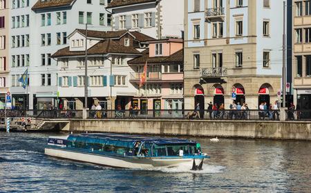 Zürich, Zwitserland - 15 oktober, 2017: gebouwen van de stad langs de rivier de Limmat, mensen aan de kade van de rivier, de Turicum boot passeren samen met passagiers aan boord. Zürich is de grootste stad in Zwitserland en de hoofdstad van de Zwitserse ca