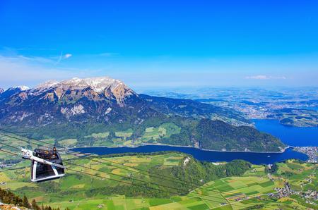 Mt. Stanserhorn, Zwitserland - 7 mei, 2016: een gondel van de Stanserhorn CabriO kabelbaan naar beneden vanaf de top van de Stanserhorn berg. Mt. Pilatus op de achtergrond. De Stanserhorn CabriO is 's werelds eerste dubbeldeks open top kabel Stockfoto - 89801796
