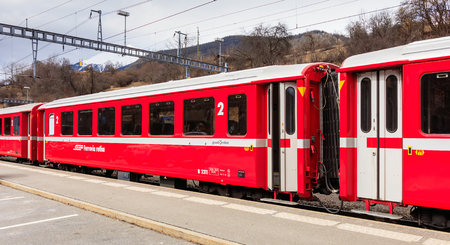 Filisur, Switzerland - 3 March, 2017: a train of the Rhaetian Railway company at a platform of the Filisur railway station. The Rhaetian Railway (German: Rhatische Bahn, abbreviated as RhB), is a Swiss transport company that owns the largest network of al