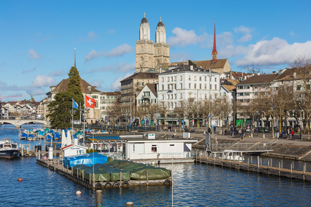 Zurich, Switzerland - 1 January, 2018: old town buildings along the Limmat river, towers of the Grossmunster cathedral and Water Church. Zurich is the largest city in Switzerland and the capital of the Swiss canton of Zurich.