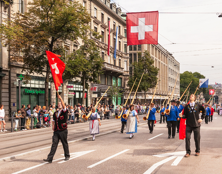 Zurich, Switzerland - 1 August, 2014: participants of the parade devoted to the Swiss National Day passing along Bahnhofstrasse street. The Swiss National Day (German: Schweizer Bundesfeier) is the na