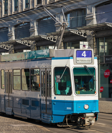 Zurich, Switzerland - 29 January, 2017: a tram passing along the Limmatquai quay. Trams have been a consistent part of Zurichs cityscape since the 1880s, when the first horse-drawn tram ran, electrified from the 1890s.
