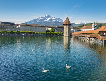 Springtime view in the city of Lucerne, Switzerland: the Reuss river and buildings along it, Water Tower, Chapel Bridge and the Jesuit Church, summit of Mt. Pilatus in the background. Imagens