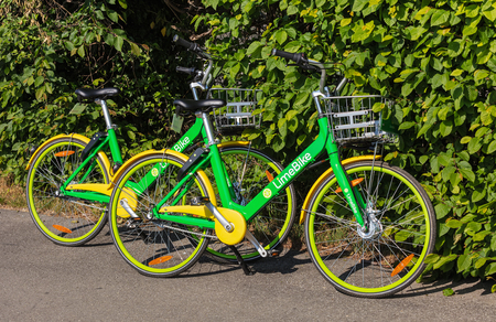 Zurich, Switzerland - May 11, 2018: two LimeBikes parked on the street. LimeBike operates a fleet of free-floating rental bikes throughout Zurich.