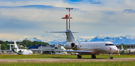 Kloten, Switzerland - May 4, 2015: view at Zurich Airport with a Bombardier Global 5000 airplane in the forground and summits of the Alps in the background. The Bombardier Global Express is a large cabin, ultra long range business jet manufactured by Bomb