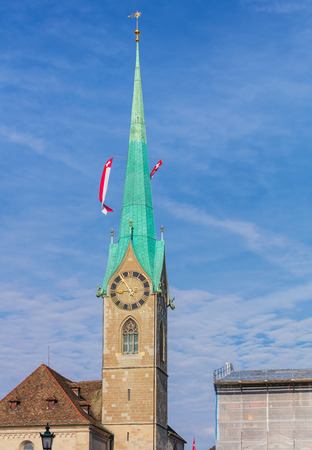 Tower of the Fraumunster cathedral in the city of Zurich, decorated with flags of Switzerland. The tower is a well-known architectural landmark of the city.