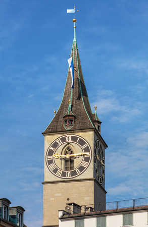 Tower of the St. Peter Church in the city of Zurich, decorated with flag of Zurich. The tower is a well-known architectural landmark of the city.