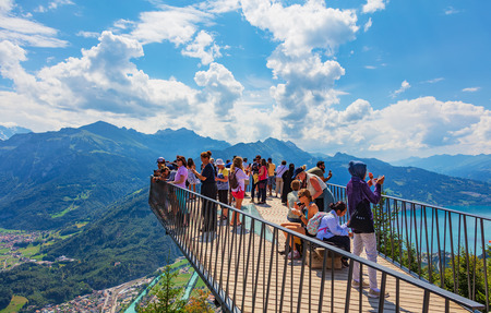 Mt. Harder, Switzerland - August 7, 2018: people on the observation platform on the Harderkulm. The Harderkulm, also referred to as Harder Kulm, is a summit of Mt. Harder, overlooking the towns of Interlaken and Unterseen in Switzerland.