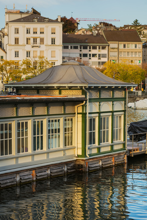 Zurich, Switzerland - October 1, 2017: partial view of the Frauenbad building on the Stadthausquai quay, old  town buildings in the background. Frauenbad is a public bath which was built for women and is still used exclusively by women. Sajtókép