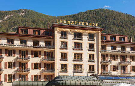 Zermatt, Switzerland - September 15, 2018: part of the facade of the building of the Grand Hotel Zermatterhof in the town of Zermatt, summits of the Alps in the background. The 5-star Grand Hotel Zermatterhof is a traditional luxury establishment, it was