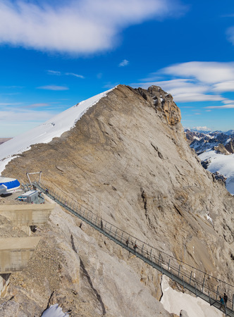 Mt. Titlis, Switzerland - October 12, 2015: view from the top of the mountain, Titlis Cliff Walk suspension bridge with people on it on the lower part of the image. The Titlis is a mountain, located o