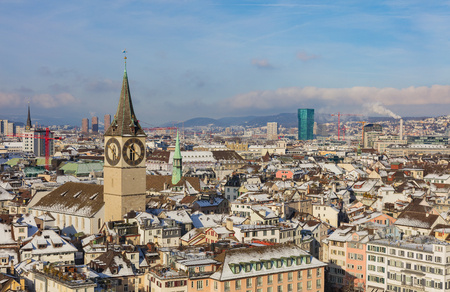 The city of Zurich in Switzerland as seen from the tower of the Grossmunster cathedral in winter, tower of the St. Peter Church in the foreground. Zurich is the largest city in Switzerland and the capital of the Swiss canton of Zurich.