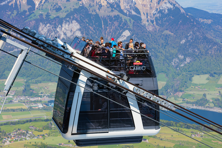 Mt. Stanserhorn, Switzerland - May 7, 2016: people in a gondola of the Stanserhorn Cabrio overhead cable car at the station on the top of the mountain. The Stanserhorn Cabrio is the worlds first double deck open top overhead cable car, it carries 60 pass Redactioneel