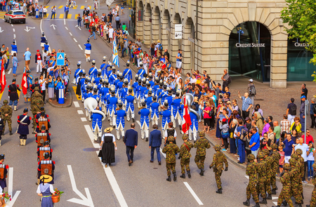 Zurich, Switzerland - August 1, 2016: participants of the parade devoted to the Swiss National Day passing along Uraniastrasse street in the city of Zurich. The Swiss National Day is the national holiday of Switzerland, celebrated on 1 August.