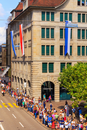 Zurich, Switzerland - August 1, 2016: people on Uraniastrasse street in the city of Zurich waiting for the parade devoted to the Swiss National Day. The Swiss National Day is the national holiday of Switzerland, celebrated on 1 August.