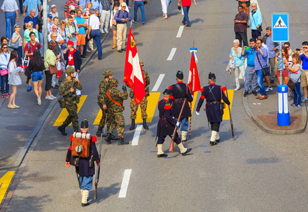 Zurich, Switzerland - August 1, 2016: participants of the parade devoted to the Swiss National Day on Uraniastrasse street in the city of Zurich. The Swiss National Day is the national holiday of Switzerland, celebrated on 1 August.