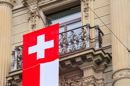Zurich, Switzerland - August 1, 2016: a balcony of the Credit Suisse building at Paradeplatz square in the city of Zurich decorated with a flag of Switzerland for the Swiss National Day celebration. The Credit Suisse Group AG is a Swiss multinational inve