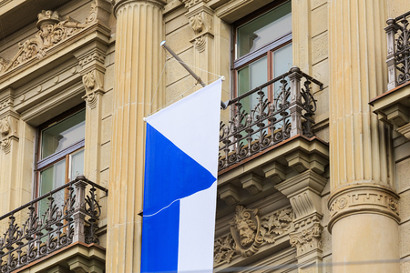 Zurich, Switzerland - August 1, 2016: a balcony of the Credit Suisse building at Paradeplatz square in the city of Zurich decorated with a flag of Zurich for the Swiss National Day celebration. The Credit Suisse Group AG is a Swiss multinational investmen Sajtókép