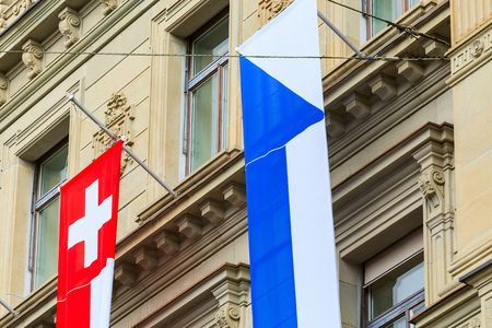 Zurich, Switzerland - August 1, 2016: part of the facade of the Credit Suisse building at Paradeplatz square in the city of Zurich decorated with flags of Zurich and Switzerland for the Swiss National Day celebration. The Credit Suisse Group AG is a Swiss Sajtókép