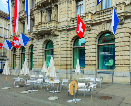 Zurich, Switzerland - August 1, 2016: facade of the Credit Suisse building on Paradeplatz square in the city of Zurich decorated with flags of Switzerland and Zurich for the Swiss National Day. The Swiss National Day is the national holiday of Switzerland