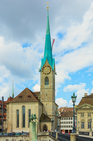 Zurich, Switzerland - August 1, 2016: the Fraumunster cathedral in the city of Zurich, people on the Munsterbrucke bridge over the Limmat river. The Fraumunster cathedral is a well-known landmark of the city of Zurich, which is the largest city in Switzer