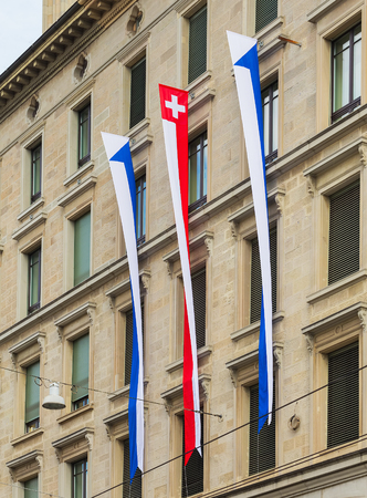 Zurich, Switzerland - August 1, 2016: part of the facade of a building in the historic part of the city of Zurich decorated with flags of Zurich and Switzerland for the Swiss National Day celebration. The Swiss National Day is the national holiday of Swit Sajtókép