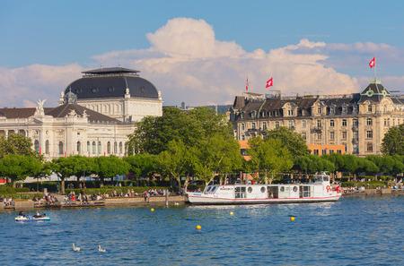 Zurich, Switzerland - May 11, 2018: people on the embankment of Lake Zurich in the city of Zurich, Zurich Opera House building in the background. Zurich is the largest city in Switzerland and the capital of the Swiss canton of Zurich. Sajtókép