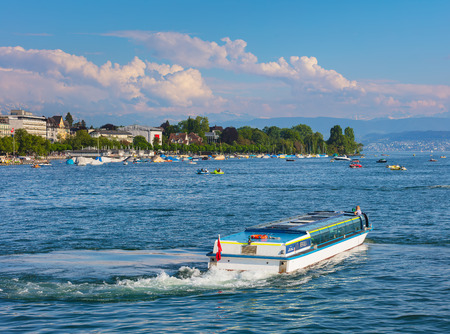 Zurich, Switzerland - May 11, 2018: Lake Zurich, summits of the Alps in the background, people in boats on the lake. Lake Zurich is a lake in Switzerland, extending southeast of the city of Zurich, which is the largest city in the country and the capital