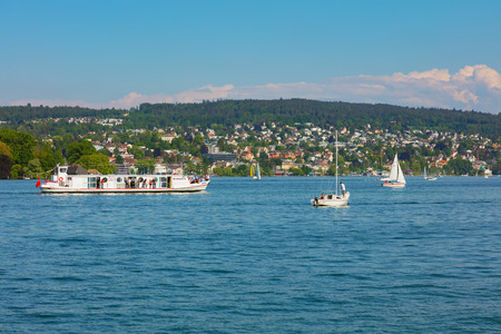 Zurich, Switzerland - May 11, 2018: people in boats on Lake Zurich, buildings of the city in the background. Lake Zurich is a lake in Switzerland, extending southeast of the city of Zurich, which is the largest city in the country and the capital of the S