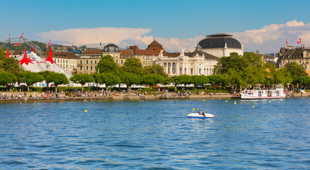 Zurich, Switzerland - May 11, 2018: people on the embankment of Lake Zurich in the city of Zurich, venue of the Circus Knie and Zurich Opera House building in the background. Zurich is the largest city in Switzerland and the capital of the Swiss canton of
