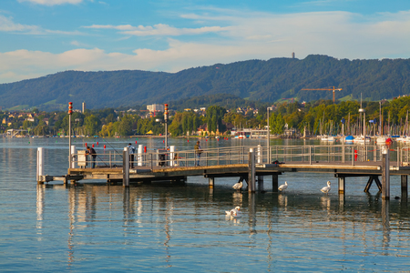 Zurich, Switzerland - August 14, 2011: people on a pier on Lake Zurich. Lake Zurich is a lake extending southeast of the city of Zurich, which is the largest city in Switzerland and the capital of the Swiss canton of Zurich. Sajtókép