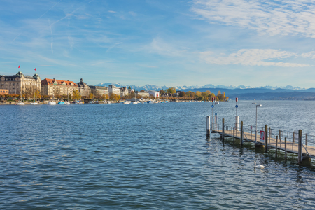 Zurich, Switzerland - October 25, 2017: Lake Zurich in the evening, buildings of the city of Zurich along it, summits of the Alps in the background. Zurich is the largest city in Switzerland and the capital of the Swiss canton of Zurich, Lake Zurich is a  Sajtókép