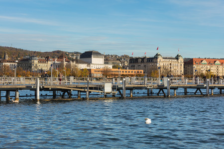 Zurich, Switzerland - October 25, 2017: pier on Lake Zurich, buildings of the city of Zurich in the background. Zurich is the largest city in Switzerland and the capital of the Swiss canton of Zurich, Lake Zurich is a lake extending southeast from it.