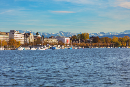 Zurich, Switzerland - October 25, 2017: buildings of the city of Zurich along Lake Zurich in the evening, summits of the Alps in the background. Zurich is the largest city in Switzerland and the capital of the Swiss canton of Zurich, Lake Zurich is a lake