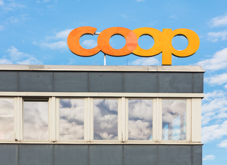 Zurich, Switzerland - October 25, 2017: upper part of a building holding a sign of the Coop Group. The Coop Group is one of Switzerlands largest retail and wholesale companies. Sajtókép