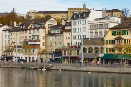 Zurich, Switzerland - October 25, 2017: buildings of the historic part of the city of Zurich along the Limmat river, people on the embankment of the river. Zurich is the largest city in Switzerland and the capital of the Swiss canton of Zurich.