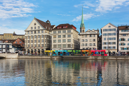 Zurich, Switzerland - October 25, 2017: buildings of the historic part of the city of Zurich along the Limmat river, people and a tram on the embankment of the river. Zurich is the largest city in Switzerland and the capital of the Swiss canton of Zurich.