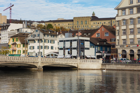 Zurich, Switzerland - October 25, 2017: buildings of the historic part of the city of Zurich along the Limmat river, building of the Swiss Federal Institute of Technology in Zurich above them, people on the embankment of the river and on the Rudolf Brun b Sajtókép