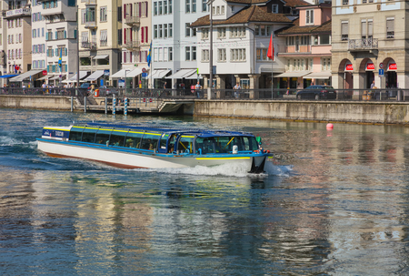 Zurich, Switzerland - June 4, 2019: Turicum motorboat with passengers on board passing along the Limmat river in the city of Zurich. The boat is owned by the Lake Zurich Navigation Company, which is a public Swiss company operating passenger ships and boa