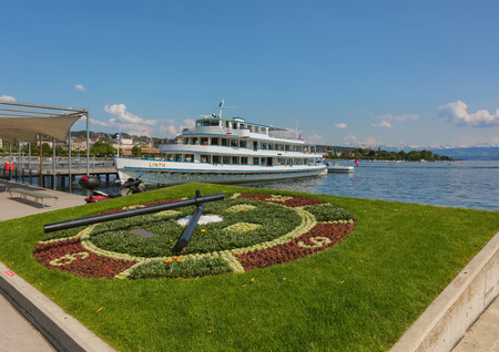 Zurich, Switzerland - June 4, 2019: the Linth boat at a pier on Lake Zurich, buildings of the city of Zurich and summits of the Alps in the background. The Linth is owned by the Lake Zurich Navigation Company, which is a Swiss company operating passenger  Sajtókép