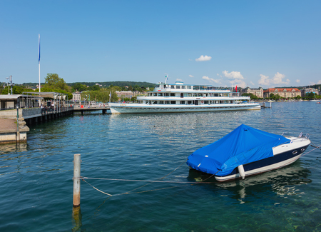 Zurich, Switzerland - June 4, 2019: the Linth passenger boat at a pier on Lake Zurich, people on the embankment of the lake, buildings of the city of Zurich in the background. The Linth is owned by the Lake Zurich Navigation Company, which is a Swiss comp