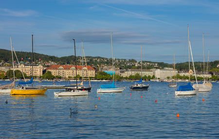 Zurich, Switzerland - June 8, 2019: boats on Lake Zurich at sunset, buildings of the city of Zurich in the background. Lake Zurich is a lake in Switzerland, extending southeast of the city of Zurich, which is the largest city in the country and the capita
