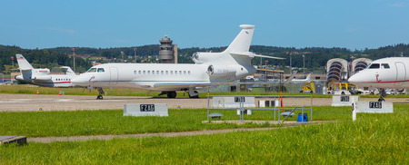Kloten, Switzerland - June 8, 2019: airplanes at Zurich Airport, a Dassault Falcon 7X in the foreground. The Dassault Falcon 7X is a large-cabin business jet manufactured by the Dassault Aviation company, Zurich Airport is the largest airport in Switzerla