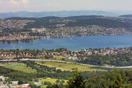Zurich, Switzerland - June 5, 2019: Lake Zurich as seen from Mt. Uetliberg. The Uetliberg is a mountain rising to 870 m and offering a panoramic view of the entire city of Zurich and Lake Zurich.