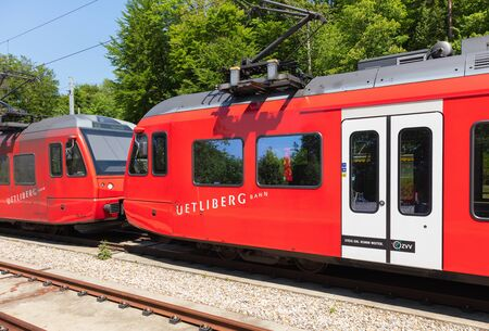 Zurich, Switzerland - June 5, 2019: two locomotives of a train of the Uetliberg railway line standing at the station on the top of Mt. Uetliberg. The Uetliberg railway line (German: Uetlibergbahn) connects the Zurich main railway station  (German: Zurich  Sajtókép