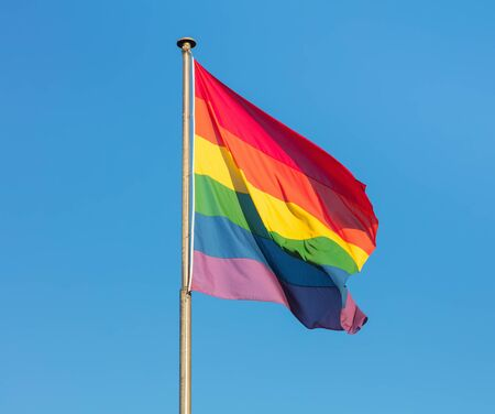 Rainbow flag of the LGBT movement against clear blue sky at sunset. Stock fotó